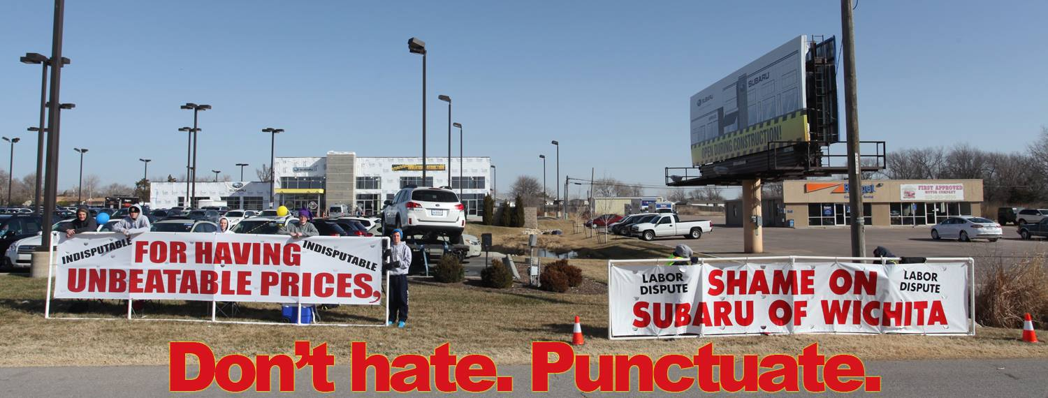 """For Having Unbeatable Prices"" ""Shame on Subaru of Wichita"" banner banners union protesters protest signs sign auto car dealership dealer automobile Kansas KS labor dispute fights back fight battle respond responds handle handled handles clever cleverly Carpenters Local 201 non-union workers large white shame drywall company construction project bullying tactics contractors wages business businesses goons rats"
