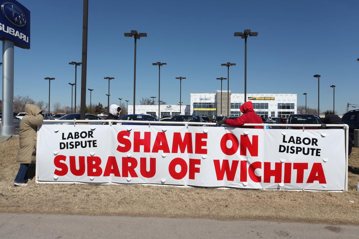 """Shame on Subaru of Wichita"" banner union protesters protest signs sign auto car dealership dealer automobile Kansas KS labor dispute fights back fight battle respond responds handle handled handles clever cleverly Carpenters Local 201 ""For Having Unbeatable Prices"" non-union workers large white banner shame drywall company construction project bullying tactics contractors wages business businesses goons rats"