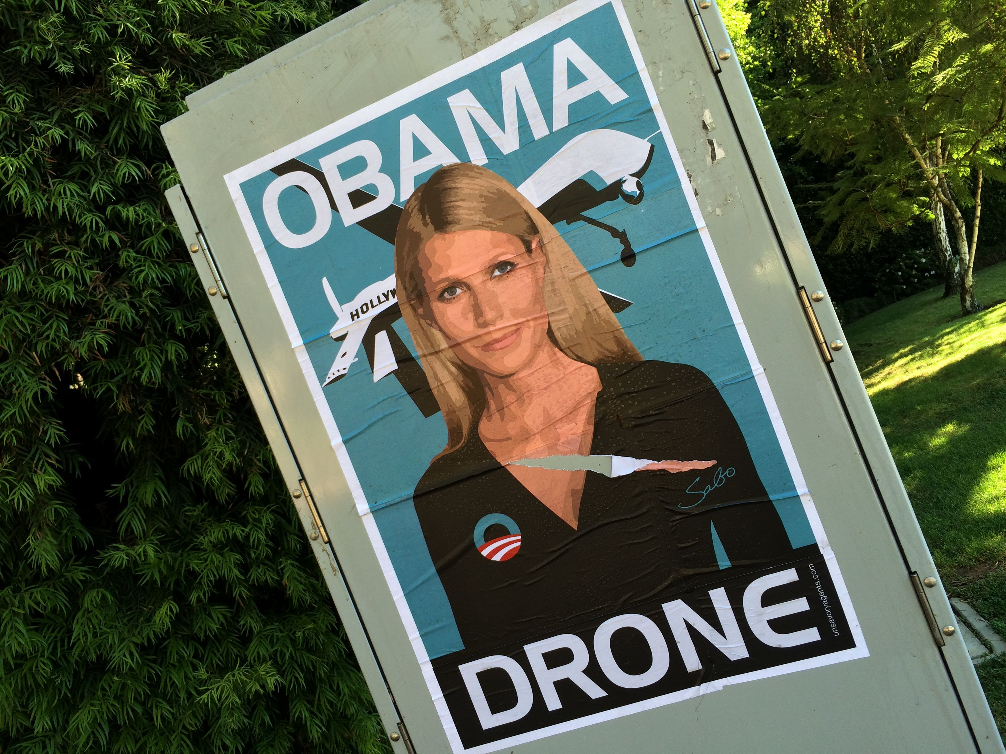 Gwyneth Paltrow Obama Drone posters poster Sabo President Obama DNC fundraiser L.A. Los Angeles Brentwood neighborhood neighbor neighbors hang hanging hung signs plaster plastering plastered traffic signal box boxes lamp posts bus benches anonymous conservative street artist provocative controversial subversive Unsavory Agents UnsavoryAgents outside political Democrats Democrat drones Predator plane planes flying background actor actress home house host hosting gala green