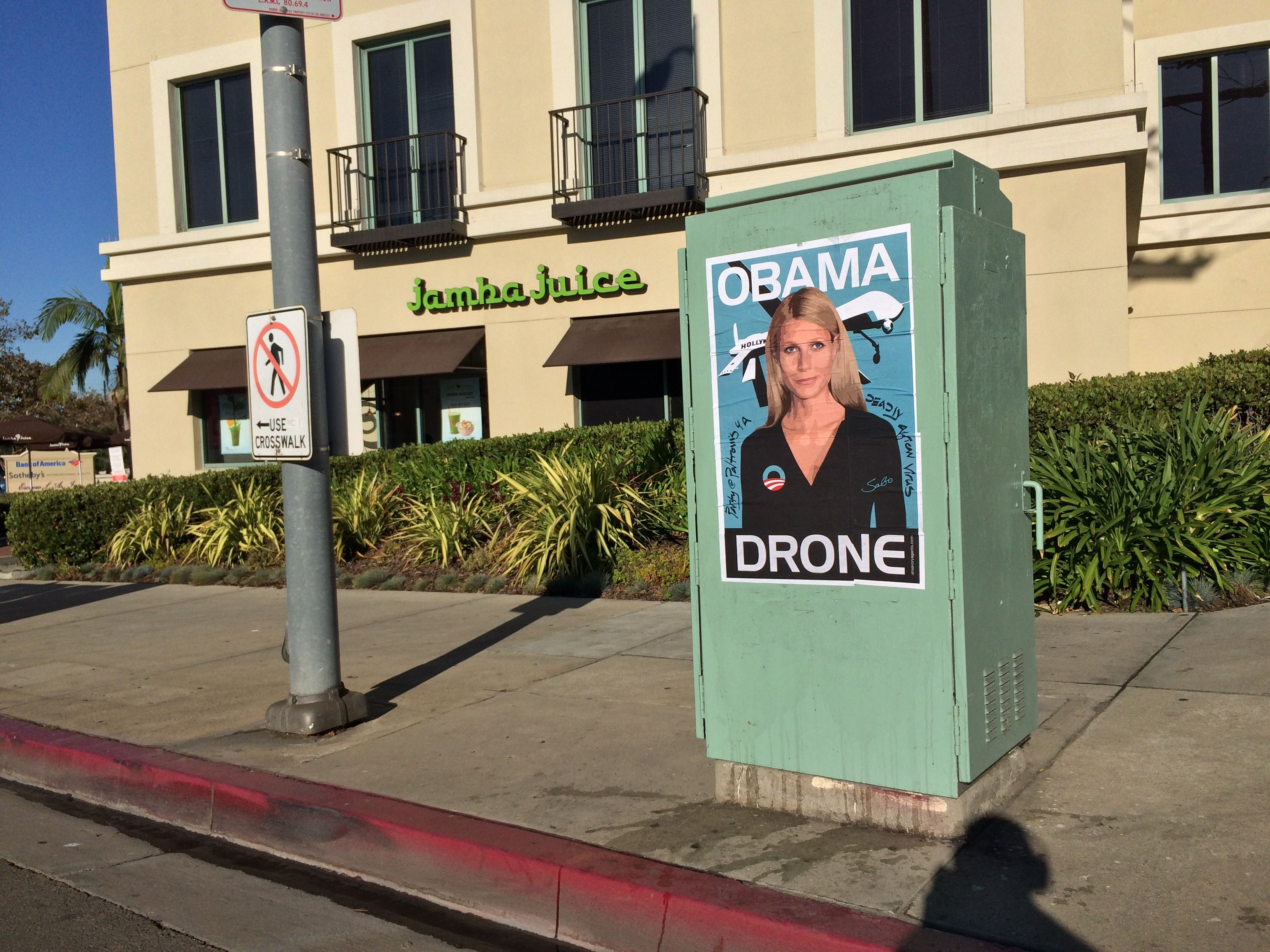 Gwyneth Paltrow Obama Drone posters poster Sabo President Obama DNC fundraiser L.A. Los Angeles Brentwood neighborhood neighbor neighbors hang hanging hung signs plaster plastering plastered traffic signal box boxes lamp posts bus benches anonymous conservative street artist provocative controversial subversive Unsavory Agents UnsavoryAgents outside political Democrats Democrat drones Predator plane planes flying background actor actress home house host hosting gala Jamba Juice