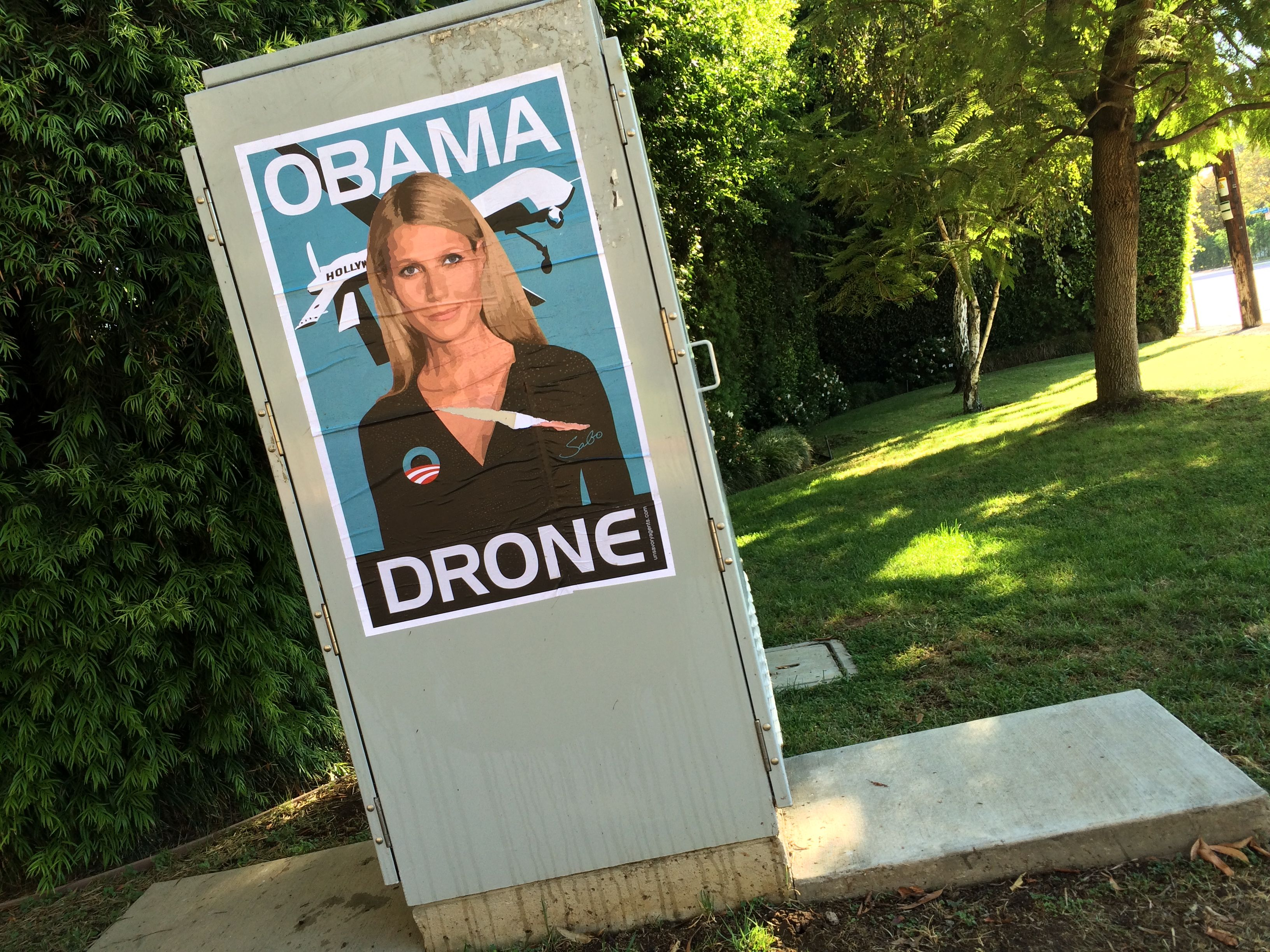 Gwyneth Paltrow Obama Drone posters poster Sabo President Obama DNC fundraiser L.A. Los Angeles Brentwood neighborhood neighbor neighbors hang hanging hung signs plaster plastering plastered traffic signal box boxes lamp posts bus benches anonymous conservative street artist provocative controversial subversive Unsavory Agents UnsavoryAgents outside political Democrats Democrat drones Predator plane planes flying background actor actress home house host hosting gala rip clean