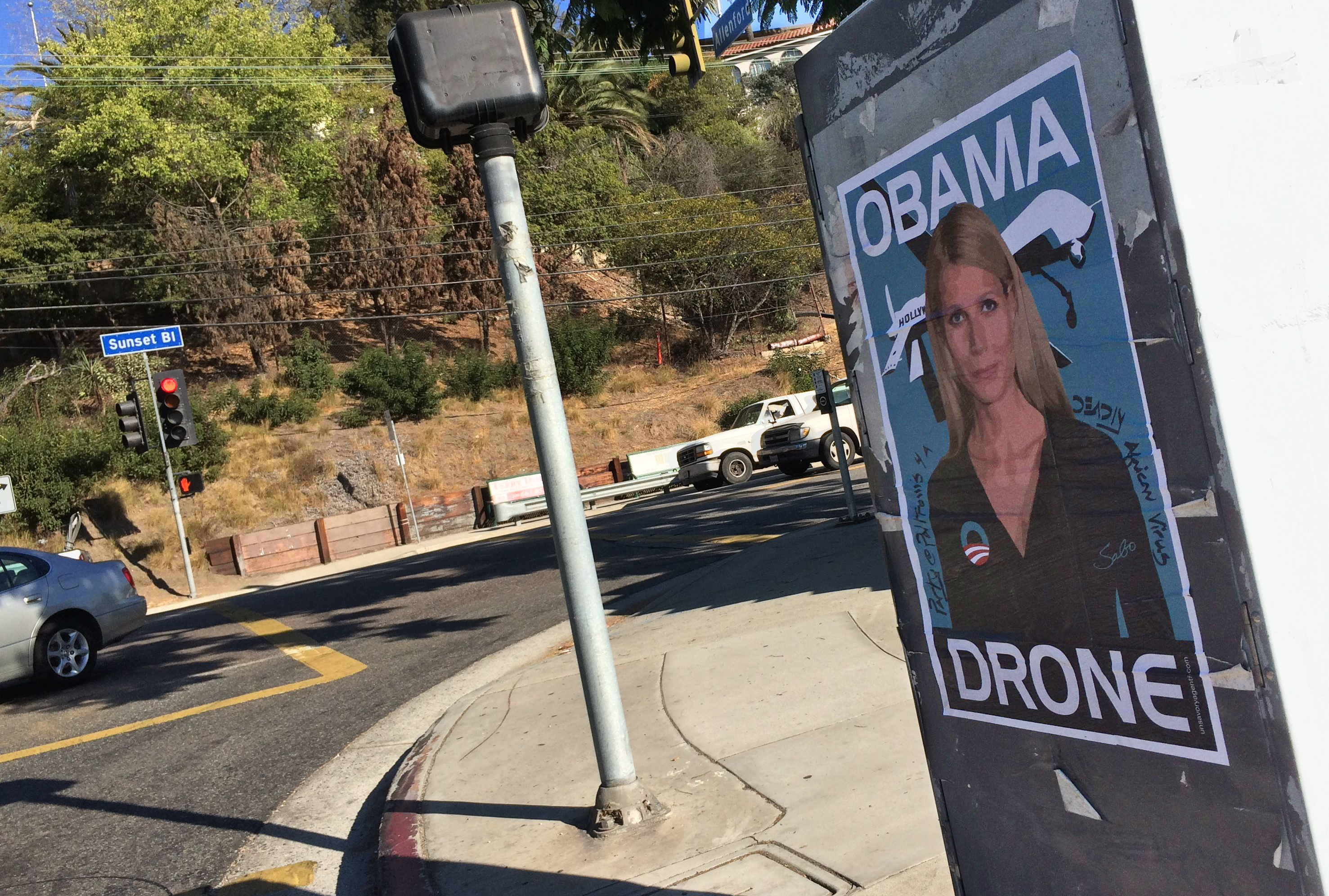 Gwyneth Paltrow Obama Drone posters poster Sabo President Obama DNC fundraiser L.A. Los Angeles Brentwood neighborhood neighbor neighbors hang hanging hung signs plaster plastering plastered traffic signal box boxes lamp posts bus benches anonymous conservative street artist provocative controversial subversive Unsavory Agents UnsavoryAgents outside political Democrats Democrat drones Predator plane planes flying background actor actress home house host hosting gala sunset 02