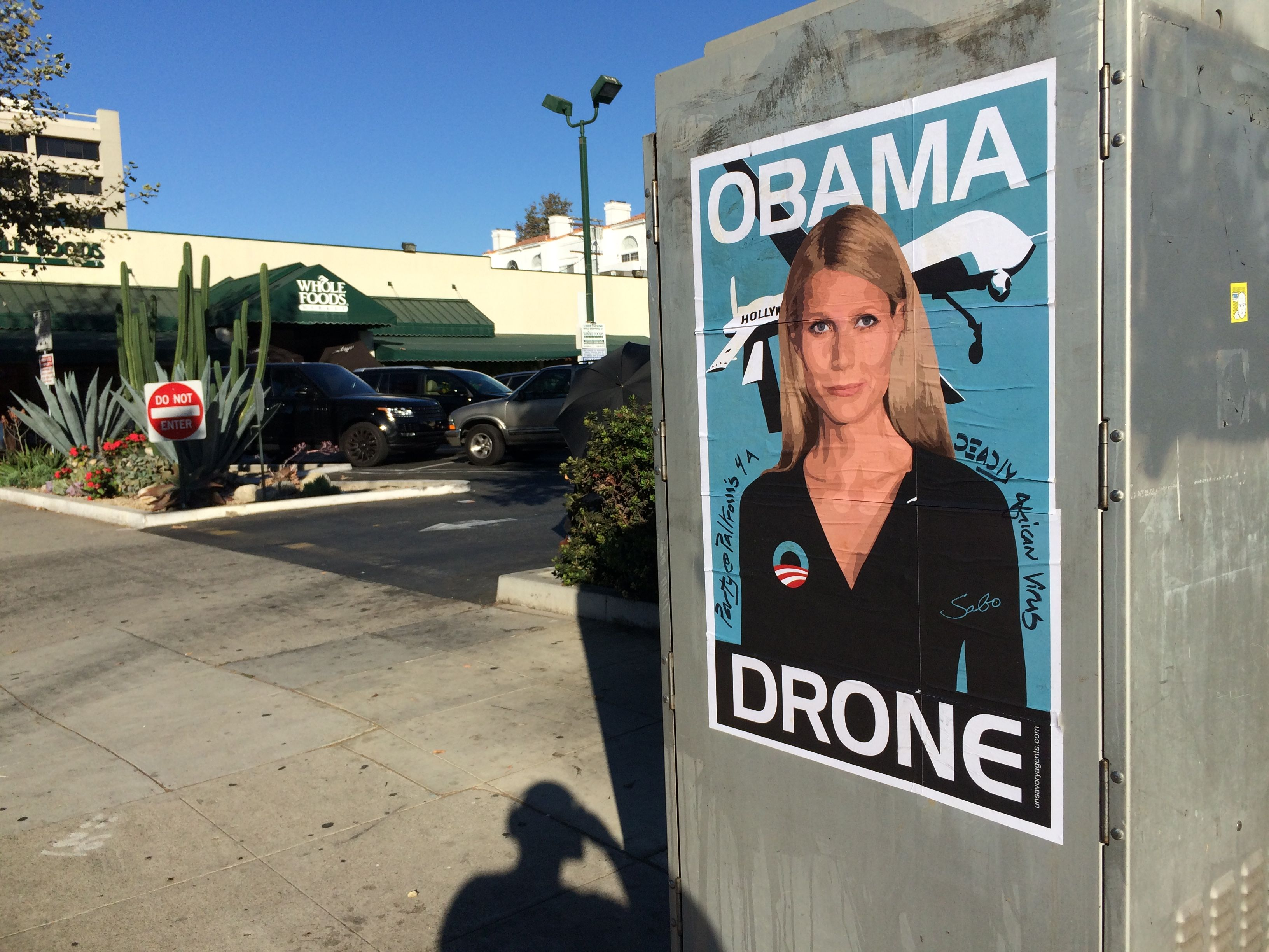 Gwyneth Paltrow Obama Drone posters poster Sabo President Obama DNC fundraiser L.A. Los Angeles Brentwood neighborhood neighbor neighbors hang hanging hung signs plaster plastering plastered traffic signal box boxes lamp posts bus benches anonymous conservative street artist provocative controversial subversive Unsavory Agents UnsavoryAgents outside political Democrats Democrat drones Predator plane planes flying background actor actress home house host hosting gala whole foods market wholefoods
